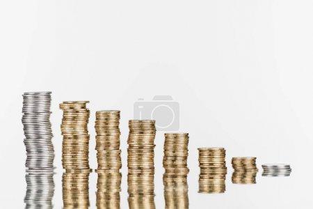 Photo pour Piles de pièces d'argent et d'or à la surface avec réflexion isolée sur blanc - image libre de droit