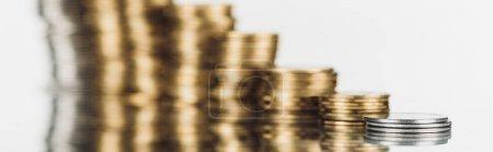 Foto de Enfoque selectivo de monedas de plata y oro apiladas sobre la superficie con una reflexión aislada en blanco, disparo panorámico. - Imagen libre de derechos