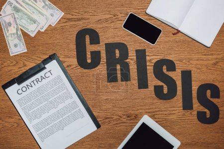 Photo for Top view of word crisis near smartphone, digital tablet, notebook, contract on clipboard and dollar banknotes on wooden desk - Royalty Free Image