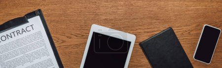Photo for Top view of digital tablet, smartphone, notebook and clipboard with contract on wooden desk, panoramic shot - Royalty Free Image