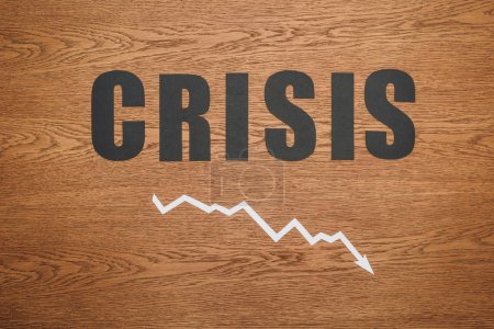 Photo for Top view of black paper cut word crisis and recession arrow on wooden desk - Royalty Free Image