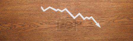 Photo for Top view of white paper cut recession arrow on wooden desk, panoramic shot - Royalty Free Image