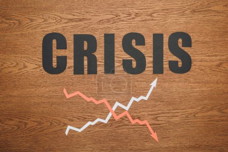 Photo for Top view of black paper cut word crisis near increase and recession arrows on wooden desk - Royalty Free Image