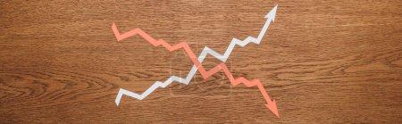 Photo pour Vue du dessus des flèches d'augmentation et de récession de la coupe de papier sur un bureau en bois, vue panoramique - image libre de droit