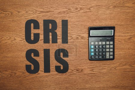 Photo for Top view of black paper cut word crisis near calculator on wooden desk - Royalty Free Image