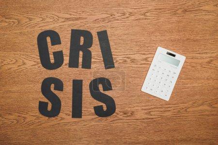 Draufsicht auf schwarzes Papier geschnitten Wortkrise in der Nähe weißer Taschenrechner auf Holztisch