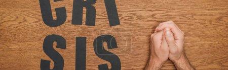 Photo pour Vue recadrée des mains pliées mâles près du papier noir couper crise mot sur bureau en bois, vue panoramique - image libre de droit