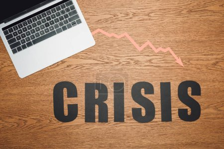 Photo pour Vue du dessus du papier noir coupe crise mot près de l'ordinateur portable et la flèche de récession sur la surface en bois - image libre de droit