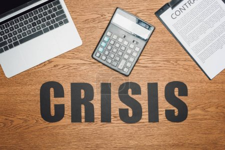 Photo for Top view of black word crisis near laptop, calculator and clipboard with contract on wooden desk - Royalty Free Image
