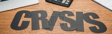 Photo pour Plan panoramique de papier noir coupe crise mot près de l'ordinateur portable, calculatrice et document sur bureau en bois - image libre de droit