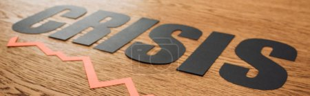 Photo for Panoramic shot of black paper cut word crisis and diagram on wooden surface with lighting - Royalty Free Image