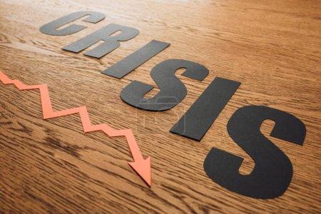 Photo pour Papier noir coupe mot crise près de la récession flèche sur la surface en bois avec éclairage - image libre de droit