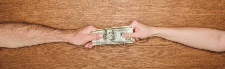 Photo for Cropped view of man and woman holding dollar banknote on wooden surface, panoramic shot - Royalty Free Image