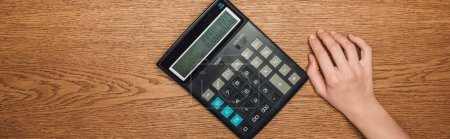 partial view of female hand near calculator with one hundred thousand on display on wooden desk, panoramic shot of