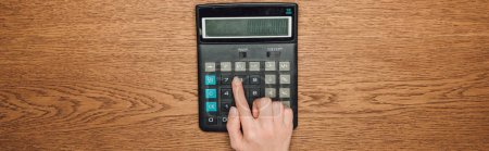 partial view of female hand on calculator with one hundred thousand on display on wooden desk, panoramic shot