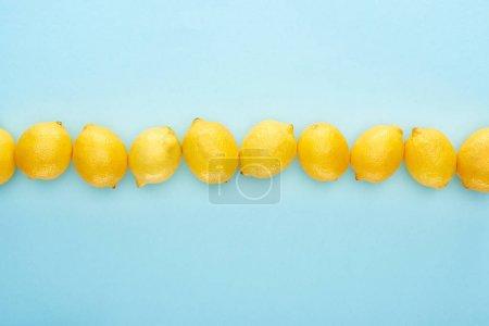 Foto de Lecho plano con limón amarillo maduro en línea sobre fondo azul - Imagen libre de derechos