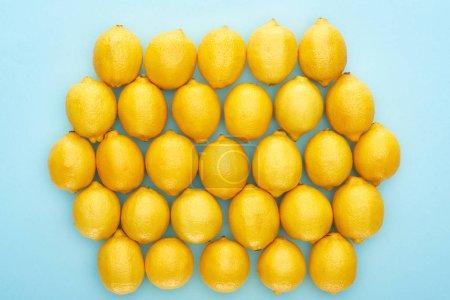 Foto de Vista superior de limones amarillos maduros sobre fondo azul - Imagen libre de derechos