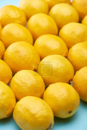 Photo for Close up view of ripe yellow lemons on blue background - Royalty Free Image