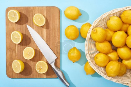 Photo for Top view of ripe yellow cut lemons on wooden cutting board with knife on blue background near whole lemons in wicker basket - Royalty Free Image