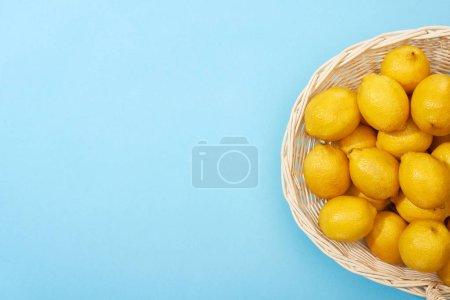 Photo for Top view of ripe yellow lemons in wicker basket on blue background with copy space - Royalty Free Image