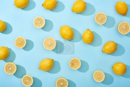 Photo for Top view of whole and cut yellow lemons on blue background - Royalty Free Image