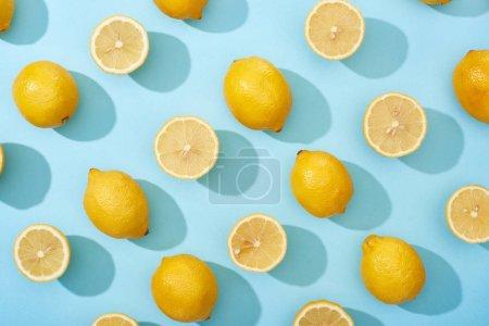 Photo pour Vue de dessus de citrons jaunes entiers et coupés sur fond bleu - image libre de droit