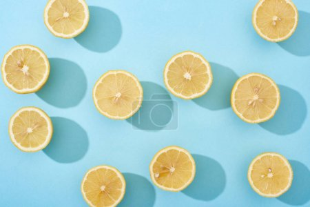 Photo for Top view of ripe cut yellow lemons on blue background - Royalty Free Image