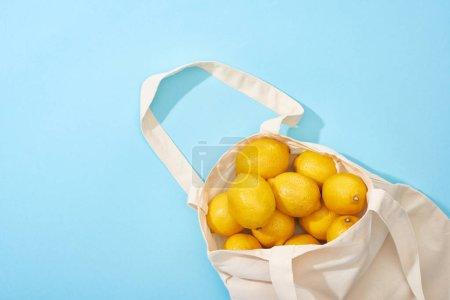 Foto de Vista superior de limones amarillos maduros en bolso ecológico de algodón sobre fondo azul - Imagen libre de derechos
