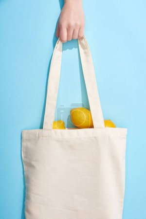 Photo for Cropped view of woman holding ripe yellow lemons in cotton bag on blue background - Royalty Free Image