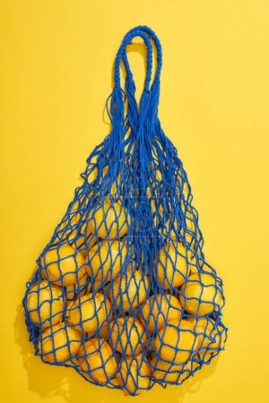 Photo for Top view of ripe lemons in string bag on yellow background - Royalty Free Image