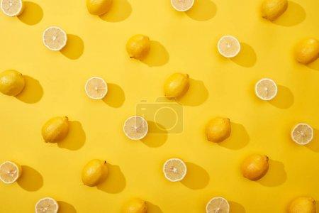 Foto de Vista superior del corte maduro y limones enteros sobre fondo amarillo - Imagen libre de derechos