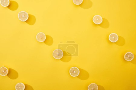 top view of ripe cut lemons on yellow background