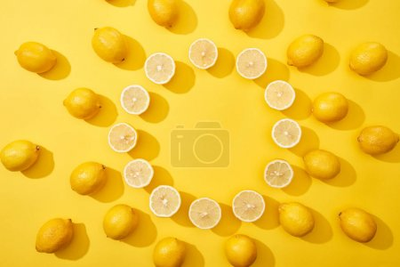 Photo for Top view of ripe cut and whole lemons arranged in round frame on yellow background with copy space - Royalty Free Image