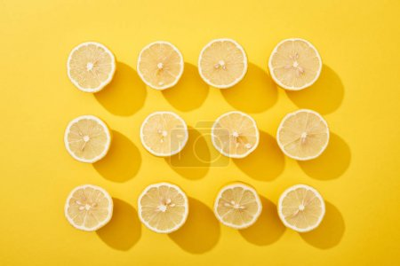 Photo for Flat lay with ripe cut lemons on yellow background - Royalty Free Image