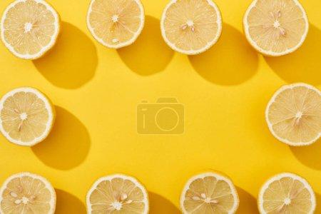 Photo pour Vue de dessus des citrons coupés mûrs disposés en cadre carré sur fond jaune avec espace de copie - image libre de droit
