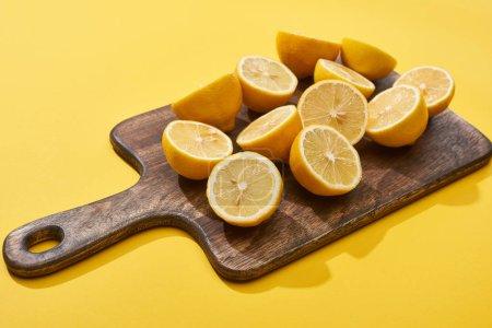 Photo pour Citrons coupés mûrs sur planche à découper en bois sur fond jaune - image libre de droit