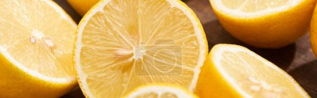 Photo pour Close up view of ripe cut lemons on wooden cutting board, panoramic shot - image libre de droit