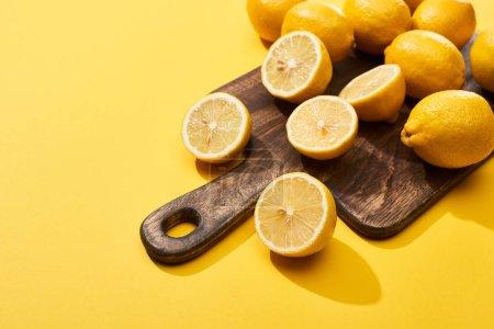 Photo pour Coupe mûre et citrons entiers sur planche à découper en bois sur fond jaune avec espace de copie - image libre de droit