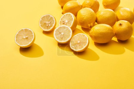 Foto de Corte maduro y limones enteros sobre fondo amarillo - Imagen libre de derechos