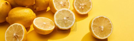 Photo pour Ripe cut and whole lemons on yellow background, panoramic shot - image libre de droit