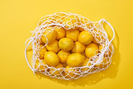 Photo for Top view of fresh ripe whole lemons in eco string bag on yellow background - Royalty Free Image