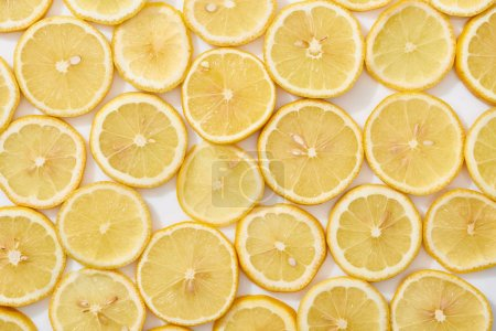 top view of ripe fresh yellow lemon slices pattern on white background