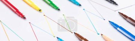 Foto de Foto panorámica de coloridas plumas de punta de fieltro sobre fondo blanco con líneas trazadas conectadas, conexión y concepto de comunicación. - Imagen libre de derechos