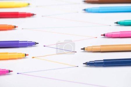 Photo pour Mise au point sélective de stylos à bout feutre colorés sur fond blanc avec lignes tracées reliées, concept de connexion et de communication - image libre de droit
