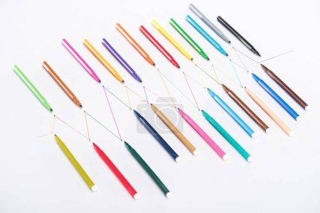 Photo pour Vue de dessus de stylos à pointe de feutre colorés sur fond blanc avec lignes tracées reliées, concept de connexion et de communication - image libre de droit