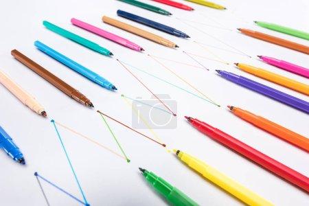 Photo pour Stylos à bout feutre multicolores sur fond blanc avec lignes tracées reliées, concept de connexion et de communication - image libre de droit