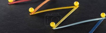 Foto de Foto panorámica de líneas interconectadas abstractas multicolores con pines sobre fondo negro, conexión y concepto de comunicación. - Imagen libre de derechos