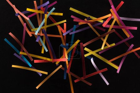 Photo pour Top view of multicolored abstract lines scattered isolated on black background, connection and communication concept - image libre de droit