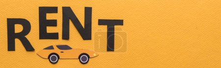 top view of paper cut car and black rent lettering on orange background with copy space, panoramic shot