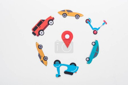 top view of paper cut vehicles arranged in round frame on white background with location mark